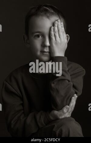black-and-white portrait of a dark-haired boy covering his eye with his hand on a black background - Stock Photo