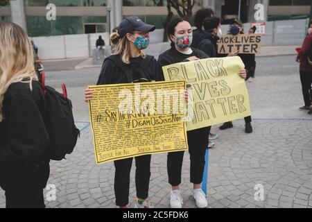 Porto, Portugal - June 6, 2020: demonstration against racial discrimination; two young women in medical masks on the street holding yellow placards - Stock Photo