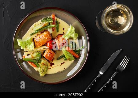 Fried piece of salmon with creamy sauce and green vegetables decorated with cherry tomato and slice of lemon. With a glass of white wine on a black ba - Stock Photo