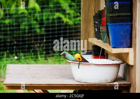 Tools and plant pots on a bench in a potting shed - Stock Photo