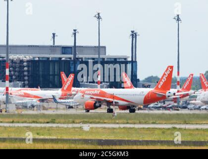 02 July 2020, Brandenburg, Schönefeld: Aircraft of the airline easyJet stand side by side at the airport in front of the BER terminal. Photo: Soeren Stache/dpa-Zentralbild/ZB - Stock Photo