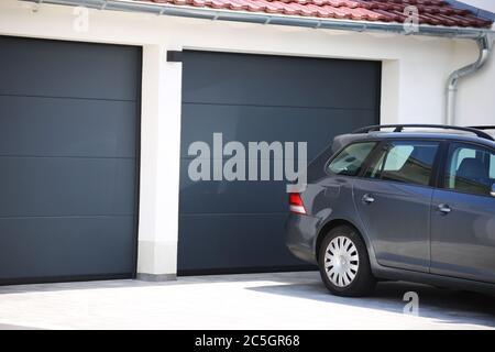 Modernes neues Garagentor (Sektionaltor) mit davor parkendem Auto