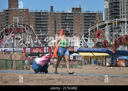 With the Coney Island Cyclone Roller Coaster in the background still closed due to the COVID-19 pandemic, a woman pulls a cooler and holds an umbrella as she makes her way along a beach path on the first day of the reopening of New York City beaches, in the Brooklyn borough of New York City, NY, July 1, 2020. Under Phase Two of the reopening of New York City during the COVID-19 pandemic, people are allowed to return to city beaches, but in-restaurant dining has been delayed due to the nationwide surge of Coronavirus cases. (Anthony Behar/Sipa USA) - Stock Photo