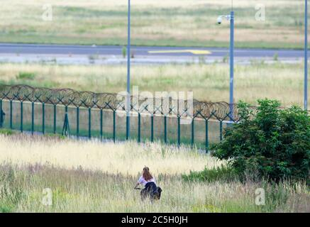 02 July 2020, Brandenburg, Schönefeld: A young woman rides her bicycle parallel to the airport fence through high grass. Photo: Soeren Stache/dpa-Zentralbild/ZB - Stock Photo