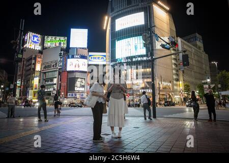 Tokyo, Japan. 02nd July, 2020. Two women wearing face masks stand in front of the Shibuya Crossing.The Japanese government has advised residents to avoid crowded places in the evenings due to the increasing numbers of Coronavirus Covid-19 infections after re-opening the economy. Credit: SOPA Images Limited/Alamy Live News - Stock Photo