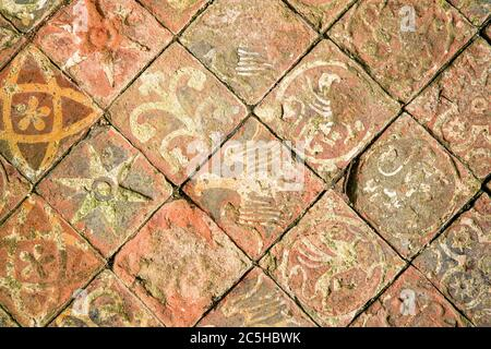 Ancient decorative quarry tile floor, depicting birds, flowers and stars. - Stock Photo