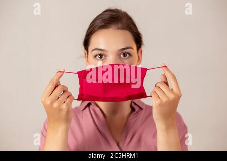 Young nurse holding a red face mask in front of her, readying to put it on. - Stock Photo