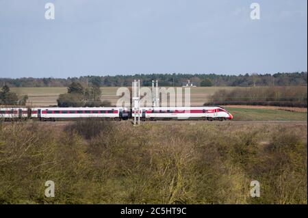High speed train in LNER livery speeding through the English countryside. - Stock Photo