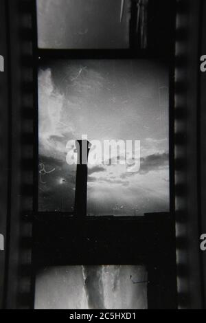 Fine 70s vintage contact print black and white photography of the air traffic control tower in the beautiful cloudy sky.