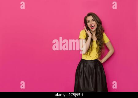 Excited beautiful woman in yellow top and black skirt is holding hand on chin, looking at camera and shouting. Three quarter length studio shot on pin