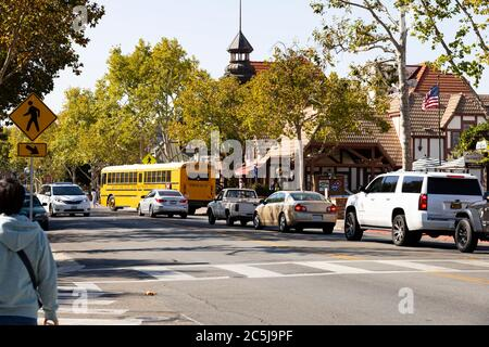 Main Street with traffic and school bus. The Danish community of Solvang, Ynez Valley, California, United States of America - Stock Photo