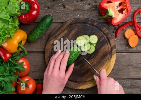Female hands cutting cucumber at table, top view - Stock Photo
