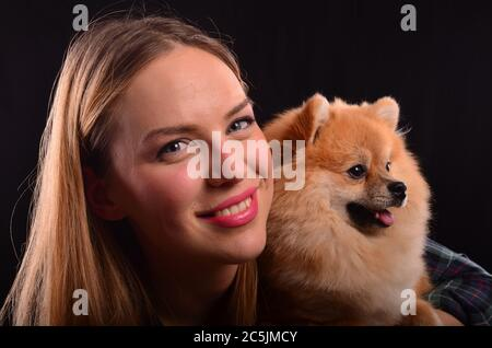 Portrait of beautiful smiling blonde girl and young Pomeranian or Spitz dog with fluffy fur - Stock Photo