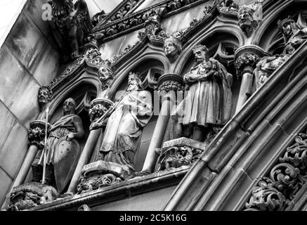 The stone carved detail of kings, in monochrome, on the exterior of Edinburgh's St Gilles Cathedral - Stock Photo