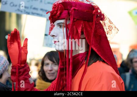 Global climate strike in St Peter's Square, Manchester UK. Extinction rebellion invisible circus red rebels. Man in profile with hand held up - Stock Photo
