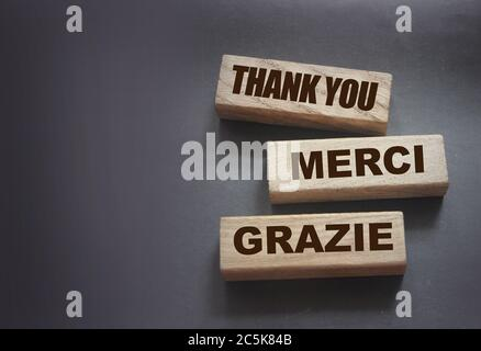 Text Thank you Merci Grazie on wooden blocks on black background. Gratitude expressed in English fFrench and Italian state of mind concept - Stock Photo