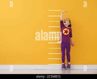 Little child is playing superhero. Kid is measuring the growth on the background of bright color wall. Girl power concept. Yellow, red and violet colo