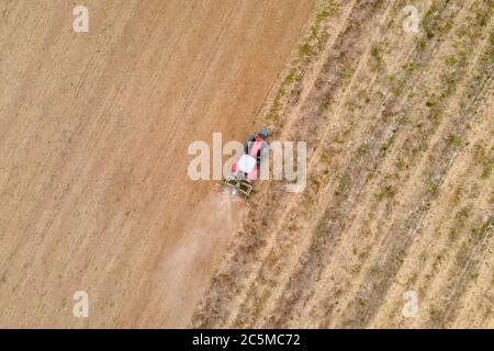 aerial drone view of a tractor  plowing in a field