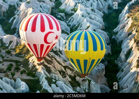 Two hot air balloons loaded with tourists fly above the spectacular landscape near Goreme in the Cappadocia region of Turkey at sunrise. - Stock Photo