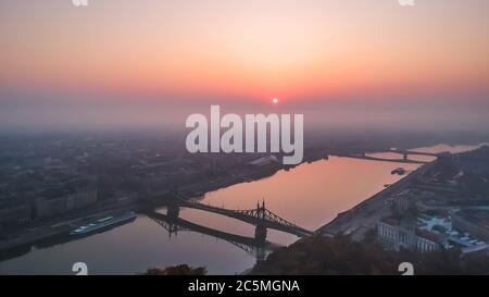 Aerial view to the Liberty Bridge and River Danube taken from Gellert Hill on sunrise in fog in Budapest, Hungary - Stock Photo