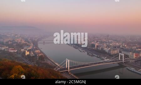 Aerial view to the Elisabeth Bridge and River Danube taken from Gellert Hill on sunrise in fog in Budapest, Hungary. - Stock Photo