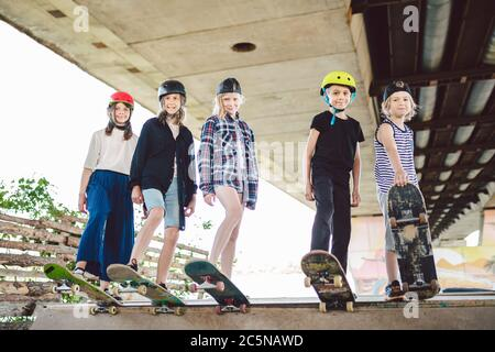 Extreme sport in city. Skateboarding Club for children. Group friends posing on ramp at skatepark. Early adolescence in skate training. Friends - Stock Photo