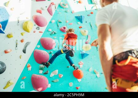 Father and teenager son at indoor climbing wall hall. Boy is hanging on the rope using a climbing harness and daddy belaying him on the floor using a
