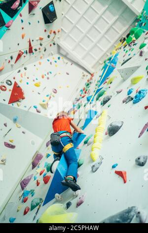 Teenager boy at indoor climbing wall hall. Boy is climbing using a top rope and climbing harness and somebody belaying him from floor. Active teenager - Stock Photo
