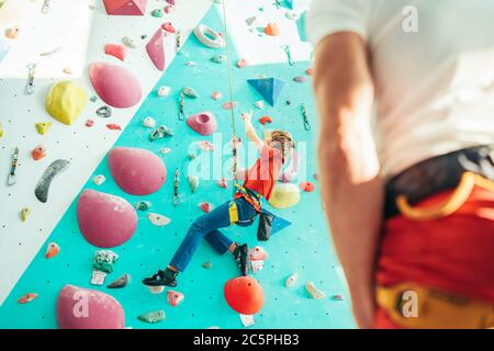 Father and teenager son at indoor climbing wall hall. Boy is hanging on the rope using a climbing harness and daddy belaying him on the floor using a - Stock Photo
