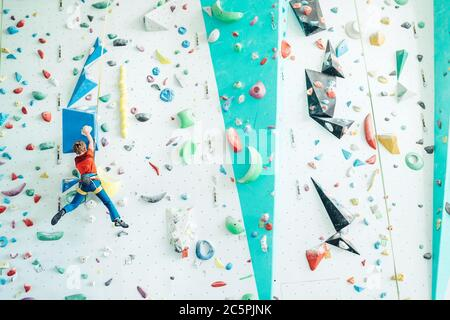 Teenager boy at indoor climbing wall hall. Boy is climbing using an auto belay system and climbing harness. Active teenager time spending concept imag