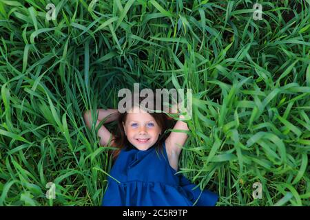 Beautiful little girl runs in the summer field - Stock Photo