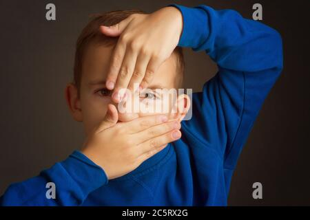 portrait of a dark-haired boy covering his face with his hands on a dark background - Stock Photo