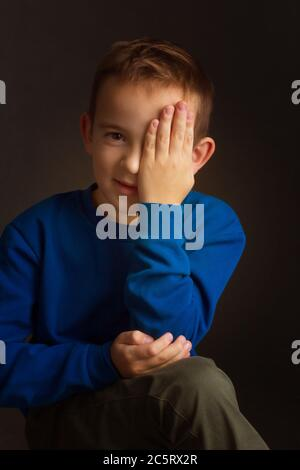portrait of a dark-haired boy covering his eye with his hand on a black background - Stock Photo