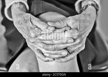 Elderly woman sitting with joined hands