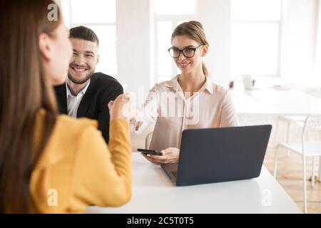 Smiling business woman with mobile phone in hand happily shaking applicant hand. Young employers spending job interview in office - Stock Photo