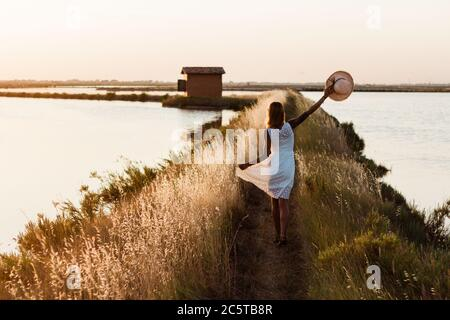 Woman in dress walking through the wheat field on a lake. Young girl enjoying life and freedom in the nature at holidays.
