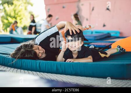 Tired children play lying on sports trampoline. Brothers cuddling on a mat in an outdoor gym. Boys rest lying on a trampoline after an acrobatics