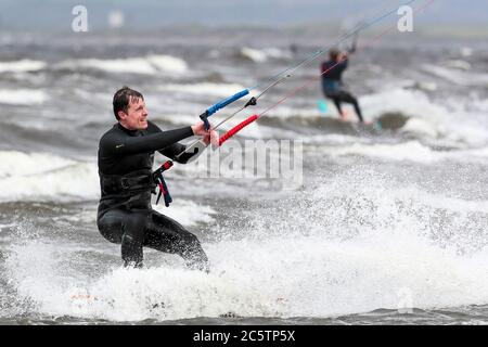 Troon, UK. 05th July, 2020. Gusty winds up to 50 mph attracted windsurfers to the beach at Troon to enjoy their hobby. on the Firth of Clyde. Credit: Findlay/Alamy Live News - Stock Photo