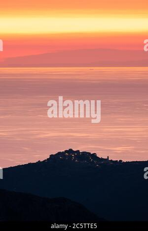 Sunset over the calm Mediterrnean sea with the silhouette of the hilltop village of Sant'Antonino in Corsica in the foreground and coast of France in - Stock Photo