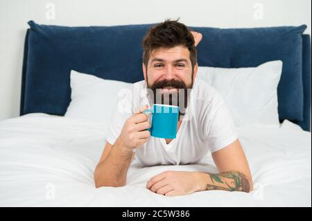 Wake up and smell coffee. Happy hipster drink coffee in morning. Bearded man enjoy coffee in bed. Hot drink. Breakfast tea. Relaxing mood. Good morning starts with coffee. - Stock Photo