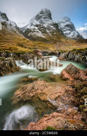 Three Sisters mountain range in Glencoe covered in layer of Winter snow with interesting rocky stream in foreground. Scottish Highlands, UK. - Stock Photo