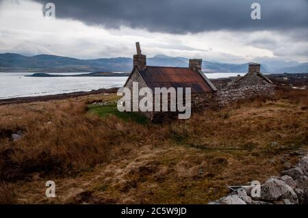 A partly ruined stone barn stands on the shore of Loch Eriboll sea loch on the far north coast of the Highlands of Scotland. - Stock Photo