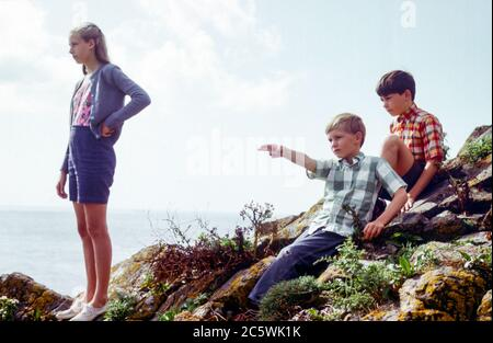 Family on cliff top walk with three children, a blonde-haired teenage girl and two younger boys on a sunny Summer day in Cornwall, UK in the 1960s on a Summer holiday - Stock Photo