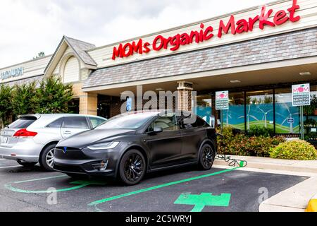 Herndon, USA - June 11, 2020: Exterior facade of Mom's Organic Market store on street in Virginia Fairfax County and Tesla model X car charging at par - Stock Photo