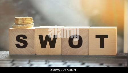 SWOT on wooden cubes and coins on computer keyboard. Business concept - Stock Photo