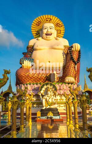Giant smiling or happy buddha statue in Wat Plai Laem Temple, Samui, Thailand in a summer day