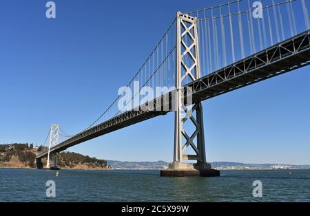 The San Francisco to Oakland Bay Bridge ad Treasure Island.  Oakland City skyline in the distance behind the grey suspension bridge.  California. - Stock Photo