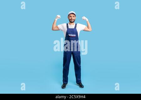 Full length cheerful handyman in overalls, cap and protective gloves standing, showing biceps, demonstrating strength. Profession of service industry, - Stock Photo