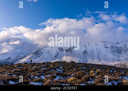 Scene view of a woman hiking against snow covered Andes mountains in winter, Esquel, Patagonia, Argentina
