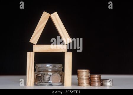 Glass bank with many world coins, house word or label on money jar and wooden home geometric blocks over table - Stock Photo